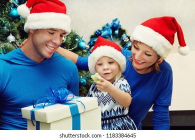 young family in Santa hats celebrating Christmas at home. father and mother giving a child present. New Year and xmas people