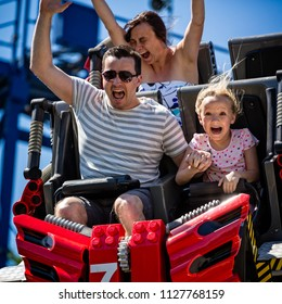 Young family screaming with arms raised on roller coaster in Florida, USA taken on 2 April 2014