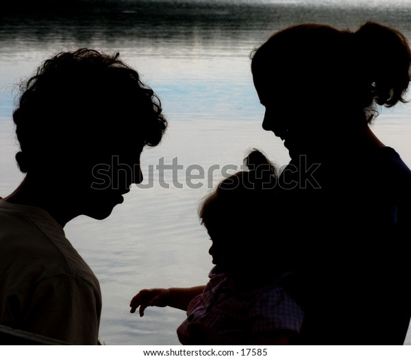 young family in silhouette at a lake