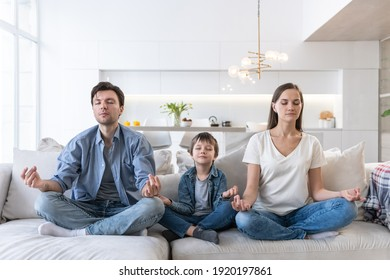 Young family sits on the sofa and meditates