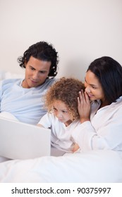 Young family sitting on the bed with laptop