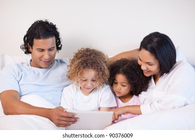 Young family sitting on the bed surfing the web
