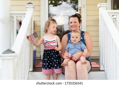 Young family sitting on the front steps celebrating the Fourth of July