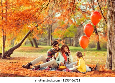 Young family sitting on a picnic blanket, eating sandwiches, having fun and enjoying a beautiful autumn day in nature