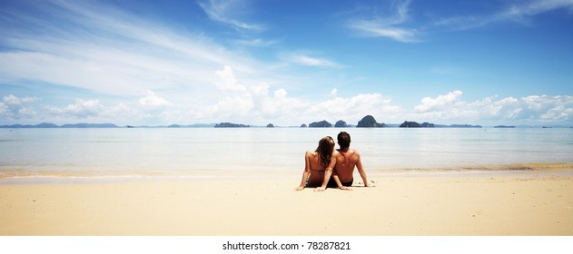 Young family sitting on warm sand by a sea and looking to sblue sky