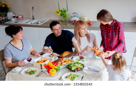 young family sitting at the table at the Easter dinner at home