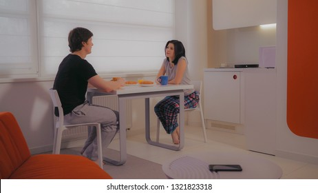 young family sitting at the table in the kitchen at home. Happy woman and man enjoy breakfast and talking.