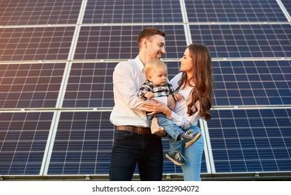Junge Familie mit einem kleinen Kind in den Armen auf einem Hintergrund von Solarpaneelen. Ein Mann und eine Frau sehen einander mit Liebe an. Bild des Solarenergiekonzepts