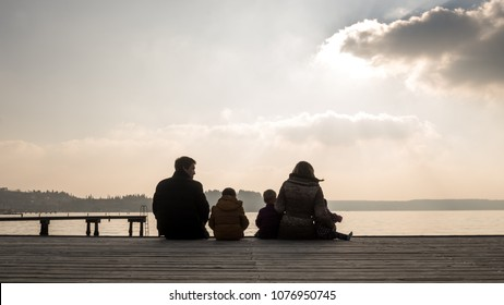 Young family with small children sitting on a wooden deck overlooking the ocean at sunset silhouetted against a glowing sky with clouds.