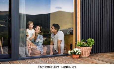 Young family with small daughter indoors, weekend away in container house in countryside.