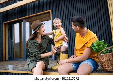 Young family with small daughter outdoors, weekend away in container house in countryside.