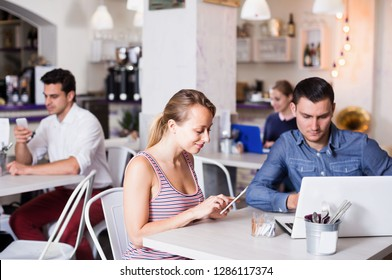 Young family spending time together in confectionery cafe and phubbing