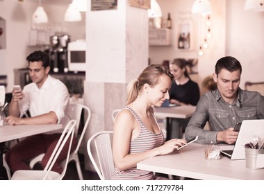 Young family spending time together in cozy cafe and phubbing