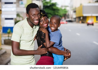 young family standing outdoors embracing looking at camera smiling.