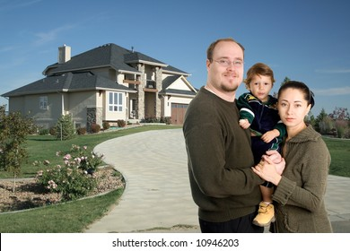 Young family standing together in front of luxury home