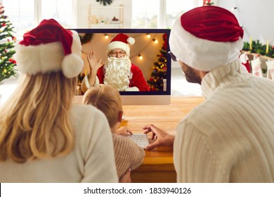 Young family staying at home on Christmas holidays and having online lockdown party. Mom, dad and son looking at computer screen during video call with Santa Claus who's waving hand to greet them
