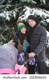A young family with a stroller walks through the winter park. A family. father and mother
