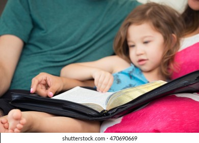 Young family studying the Word of God on the couch