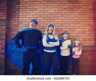 A young family of super heroes are standing outside with blue capes and masks looking up for a protection, strength or creativity concept