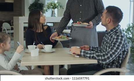Young family take a meal in cafe or restaurant. Waiter make a mistake and confuse dishes. Father and mother looking angry and disappointed.