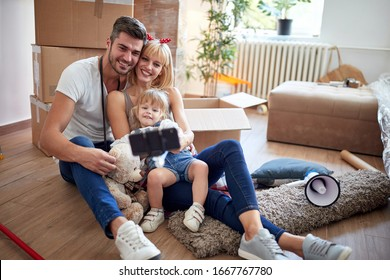young family taking selfie  in new apartment with unpacked stuff in cardboard boxes, sitting on a floor.  new apartment, new beginning, joy, playful, carefree, leisure  concept