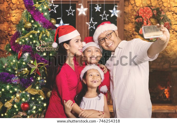 Young family taking a selfie picture together by using a smartphone near a Christmas tree in the living room