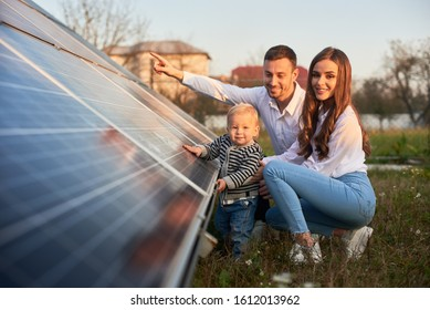 A young family of three is crouching near a photovoltaic solar panel, smiling and looking at the camera, concept of bright future