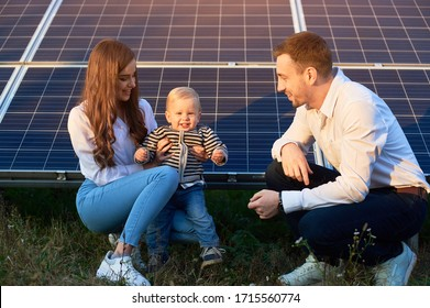 Young family of three is crouching near photovoltaic solar panel, little boy is looking at camera, parents looking at him, modern family concept