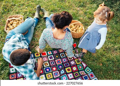 Young family of three lying in the grass in autumn before picking apples