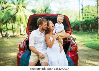 Young family three people in white clothes have picnic. Beautiful parents and son travel by car during summer vacation. Scene in park