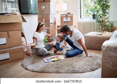 young family of three playing on a carpet in new apartment. new apartment, new beginning, joy, happiness  concept