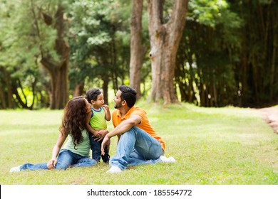 young family of three sitting together outdoors