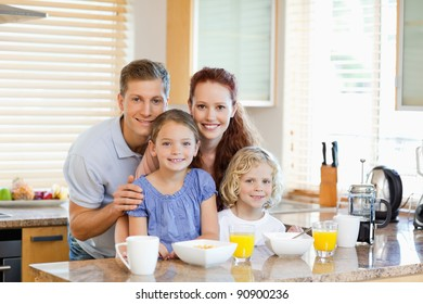 Young family together with breakfast standing behind the kitchen counter