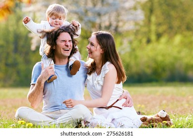Young family together in grass on the meadow