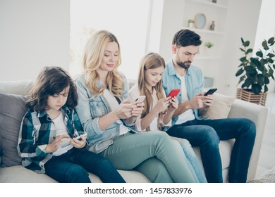 Young family two adopted children sit sofa close look telephones don't care each other addiction concept