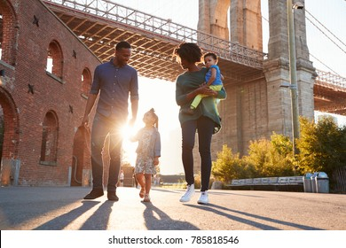 Young family with two daughters walk on a street