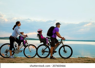 Young family with two kids go for a cycle ride on the beach at background sunset