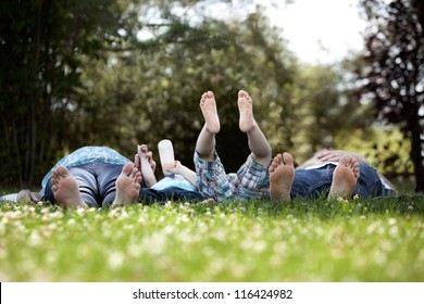 Young family with two kids and pregnant mother laying down in park with feet towards camera