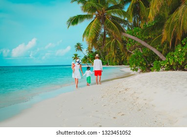 young family with two kids walking on beach