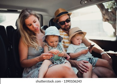 A young family with two toddler children in taxi on summer holiday.