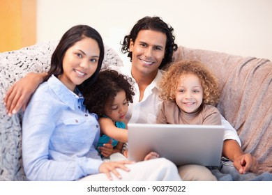 Young family using laptop on the sofa together