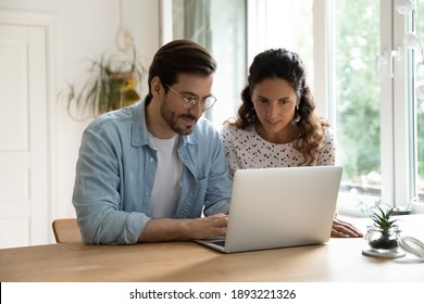 Young family using laptop together, sitting at wooden table in kitchen, attractive woman and smiling man wearing glasses surfing internet, shopping online, making purchases, booking tickets