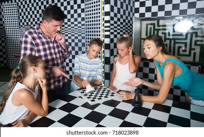 Young family is visiting of escape room stylized under chessboard.