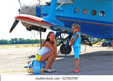young family walking on field near small airplane. Mother and daughter waiting for boarding, sad Two girls sitting on the bags near the aircraft, flight cancellation