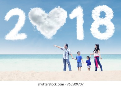 Young family walking on the shore while looking at clouds shaped numbers 2018 and heart in the blue sky