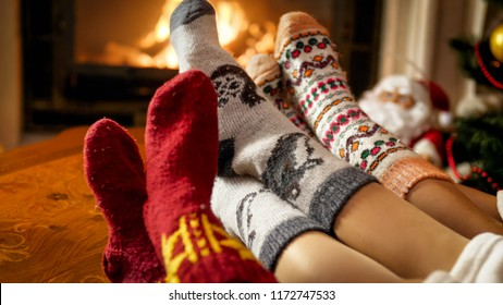 Young family in warm woolen socks warming by the fireside at house