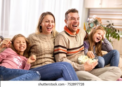 young family watching television at home. Leisure and entertainment concept