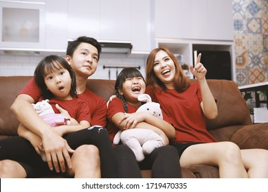 Young family watching TV together at home and having fun together