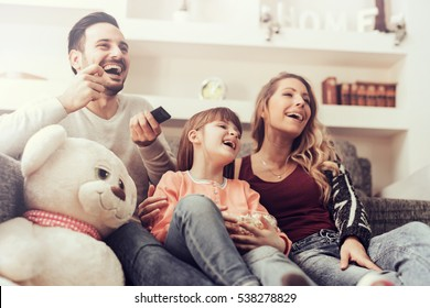Young family watching TV together at home and having fun together.