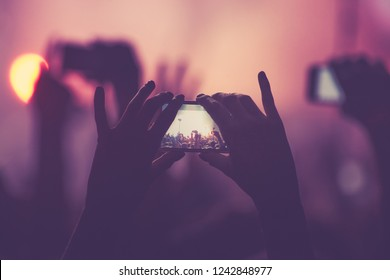Young fan girl shoot video with phone on concert in nightclub.Woman take pictures with smartphone on entertainment event in music hall.Festival audience film festival with mobile camera